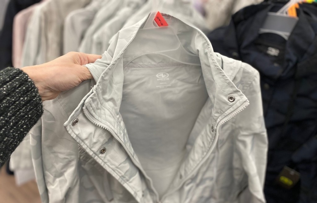 hand holding silver rain jacket jacket on hanger