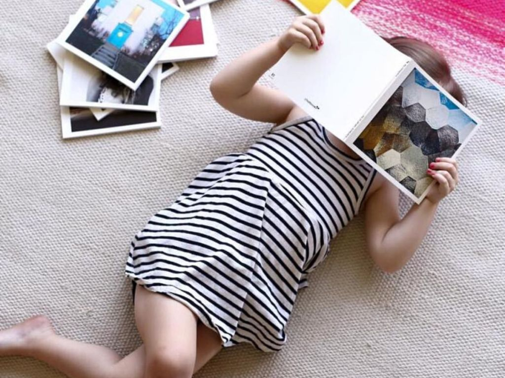 little girl laying on floor on her back reading a book held directly over her face