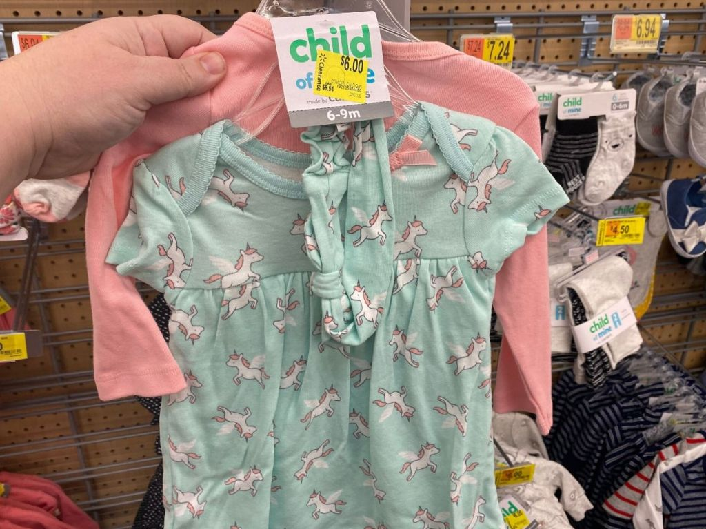 woman's hand holding three piece baby girl outfit at store