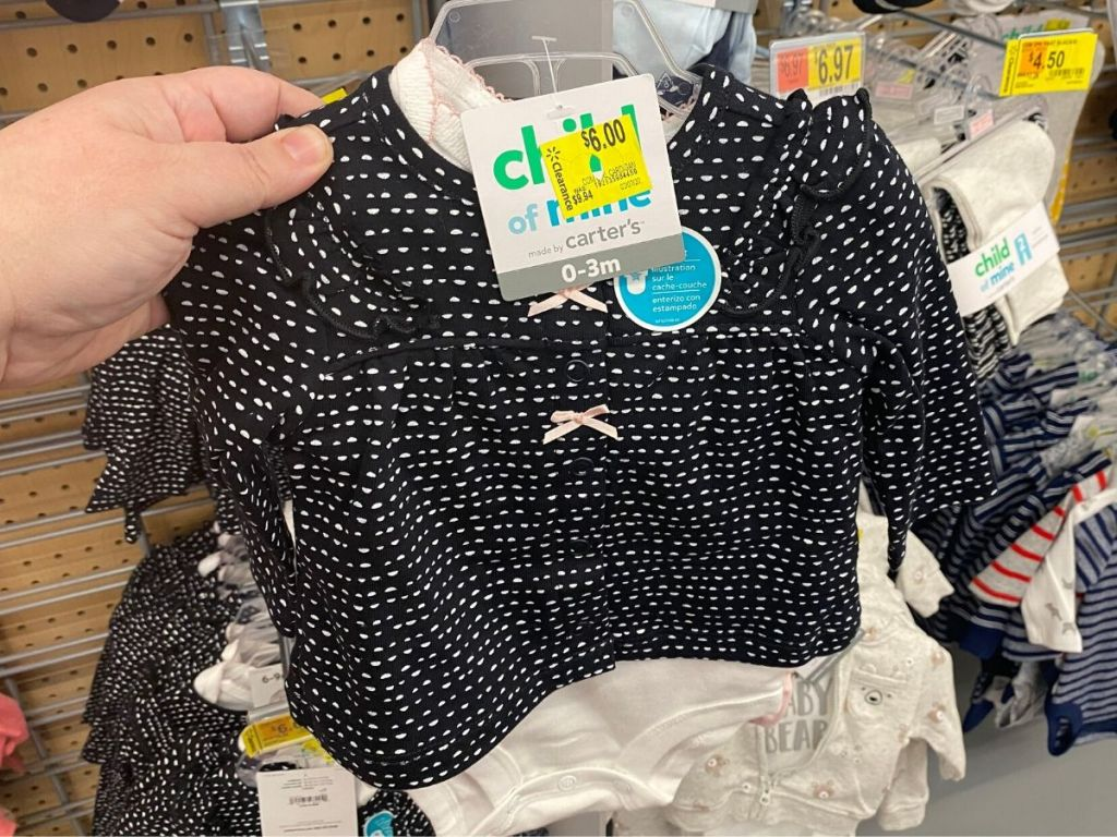 woman's hand holding 3 piece baby girl outfit in store
