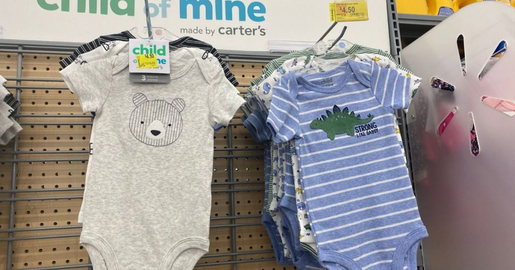 3 piece sets of onesies for babies hanging up on wall at store