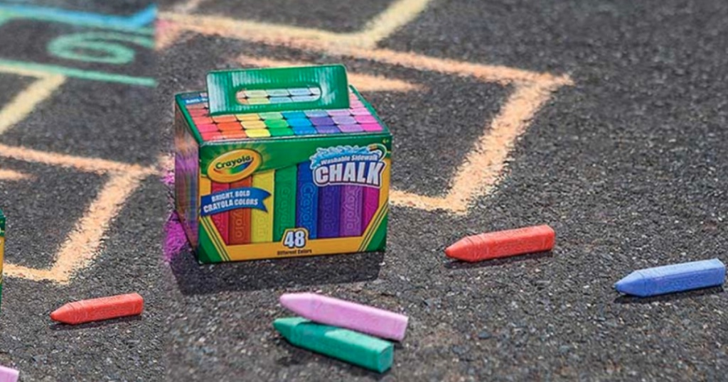 crayola sidewalk chalk box on pavement with chalk and drawings on pavement