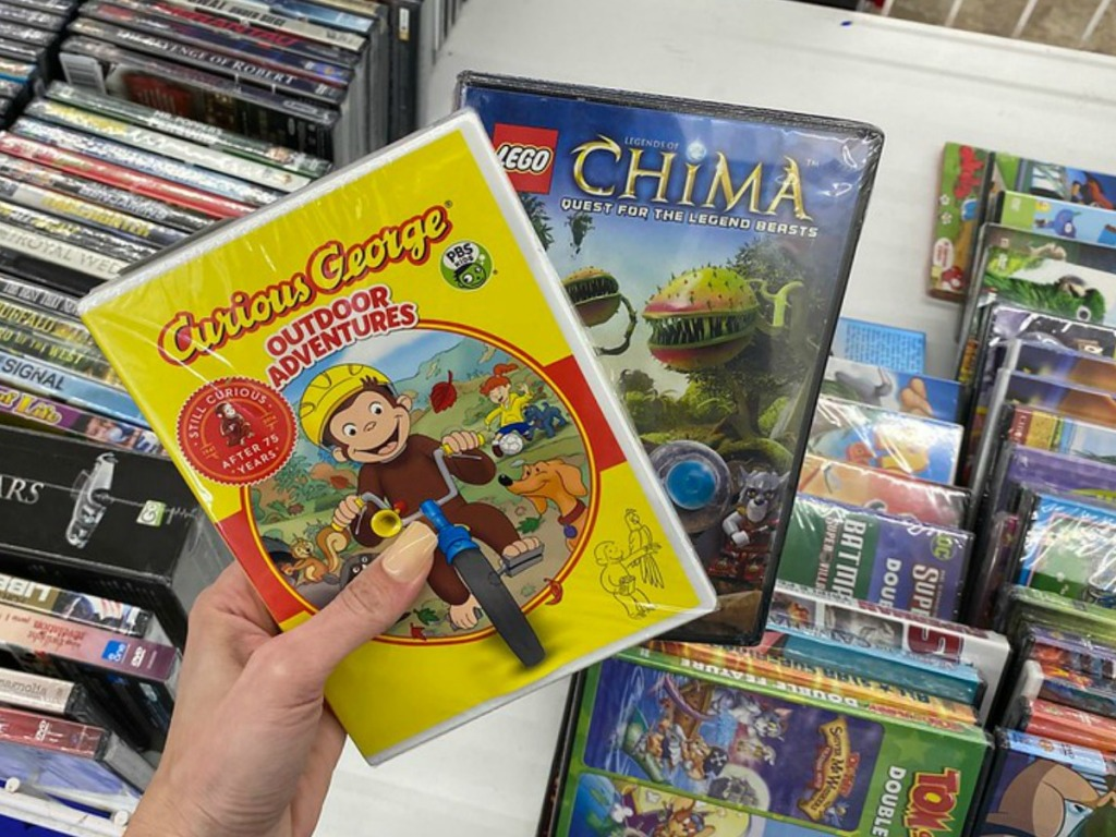 hand holding two DVDs with kids titles in store