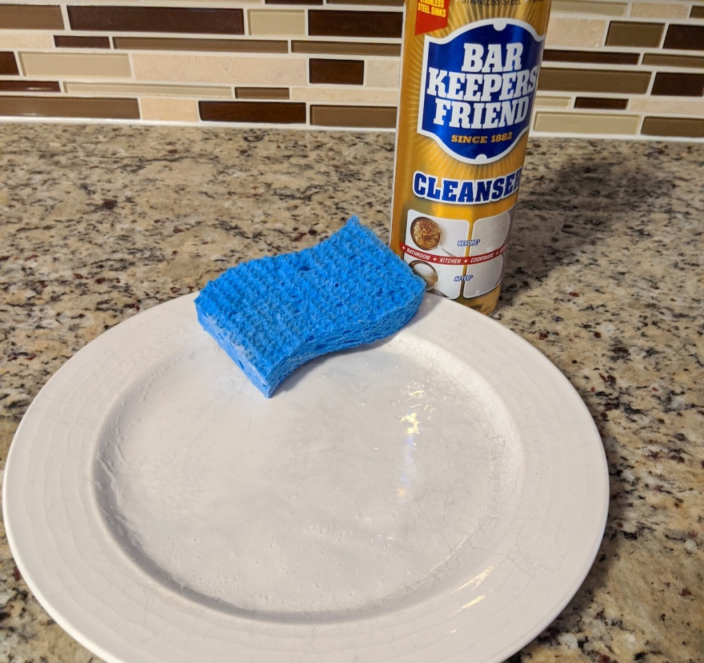 white plate with blue sponge on top next to bottle of bar keepers friend