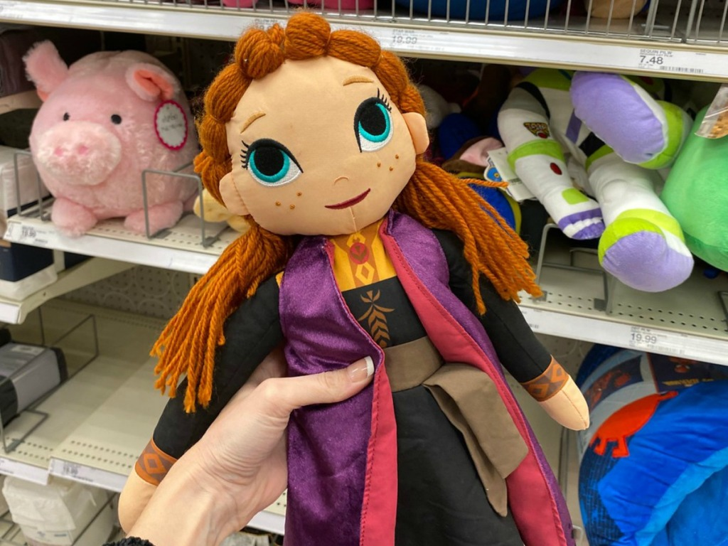 hand holding plush doll in front of store shelf