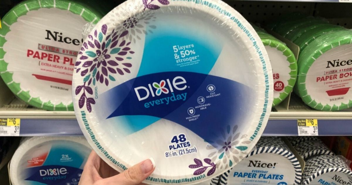 woman's hand holding up sealed package of paper plates at the store in aisle