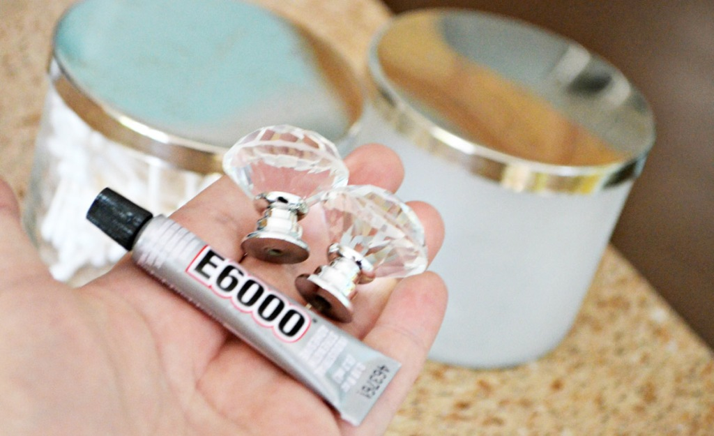 hand holding heavy duty glue and clear glass knobs