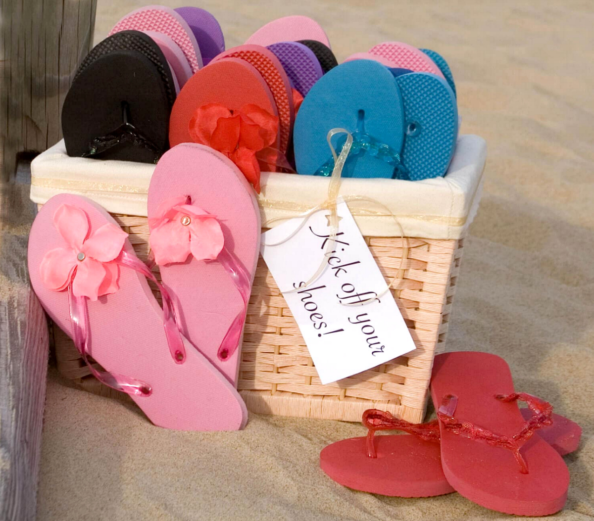 various colors of flip flops in basket in sand - dollar tree wedding
