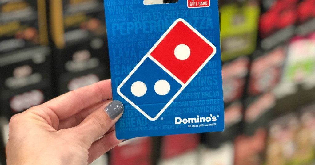 womans hand holding a dominos gift card