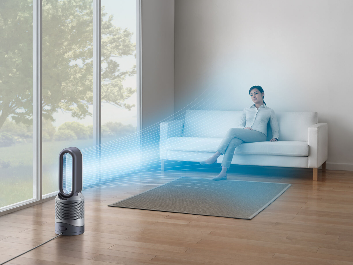 woman sitting on white couch with air purifier giving off blue rays coming toward her
