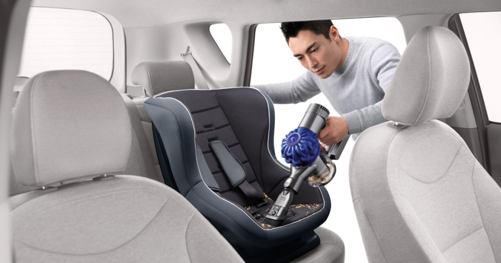 man vacuuming out car seat with dyson cordless