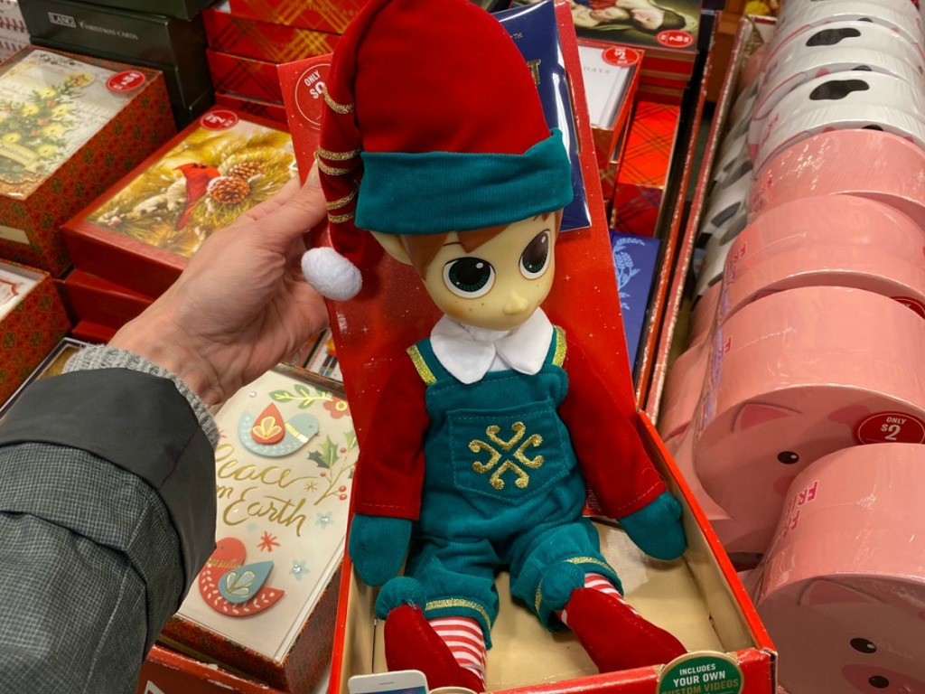 hand holding box with a plush elf in it