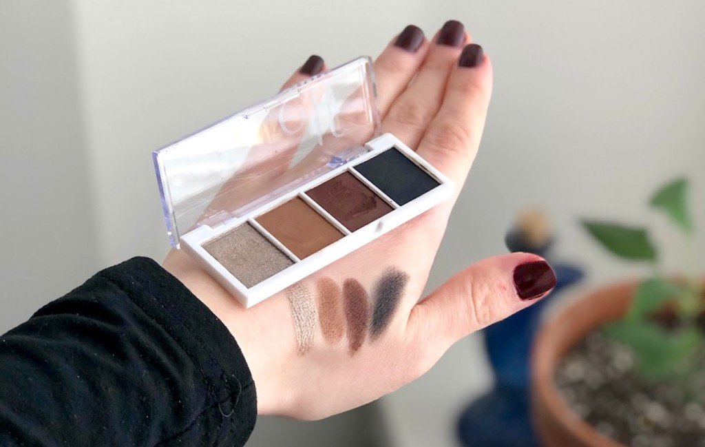 hand holding elf eyeshadow palette with eyeshadow on top of hand