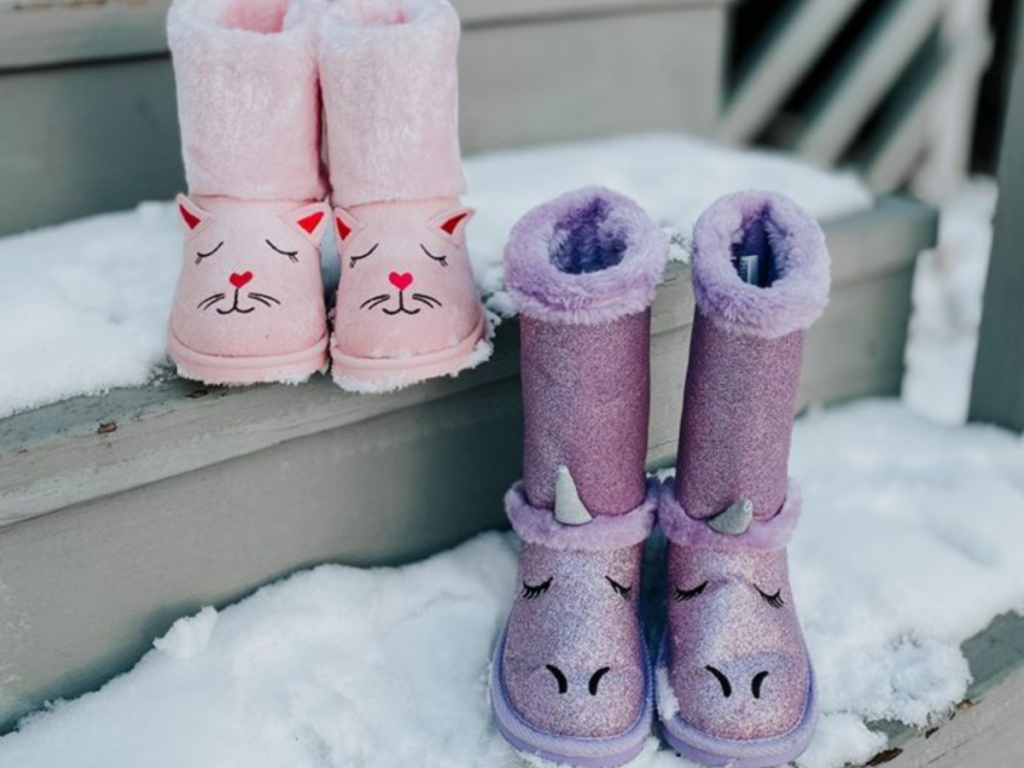 pink cat boots and purple unicorn boots on steps covered with snow
