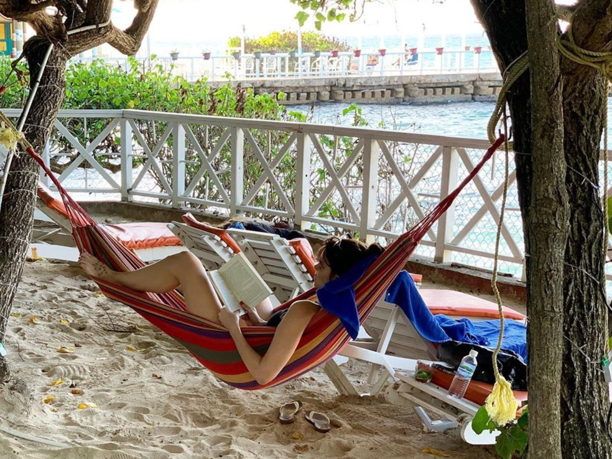 woman reading book in hammock on beach