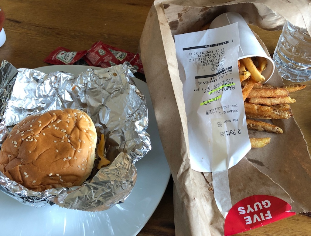 burger and fries sitting in foil and brown bag on table