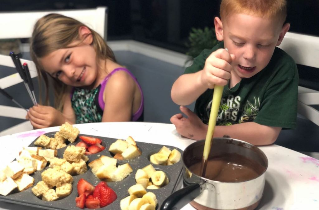 girl and boy sitting with fruit and melted bowl of chocolate fondue