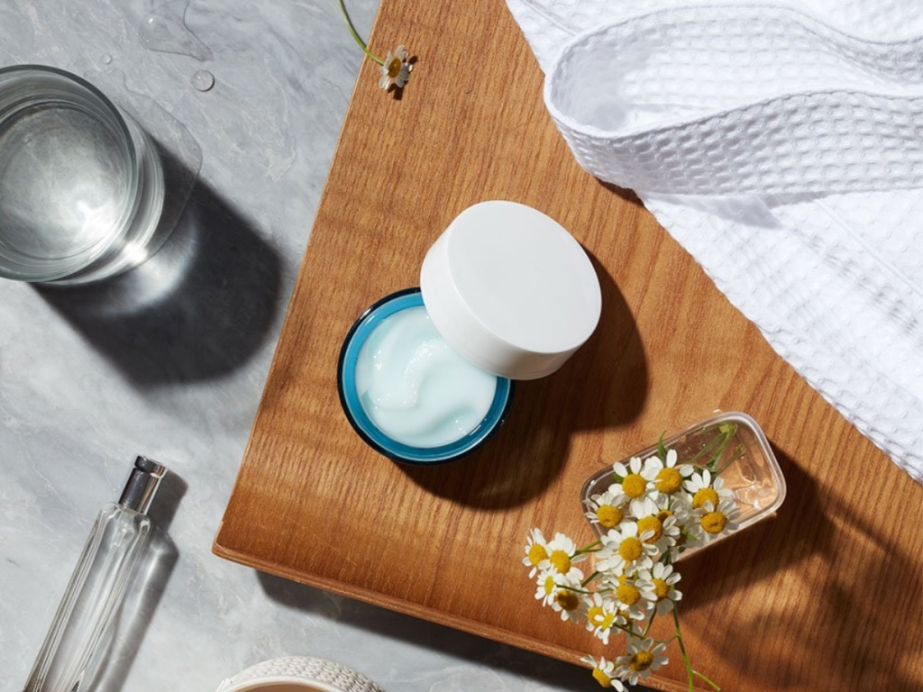 opened jar of cream on wood tray with flowers and part of a robe beside it