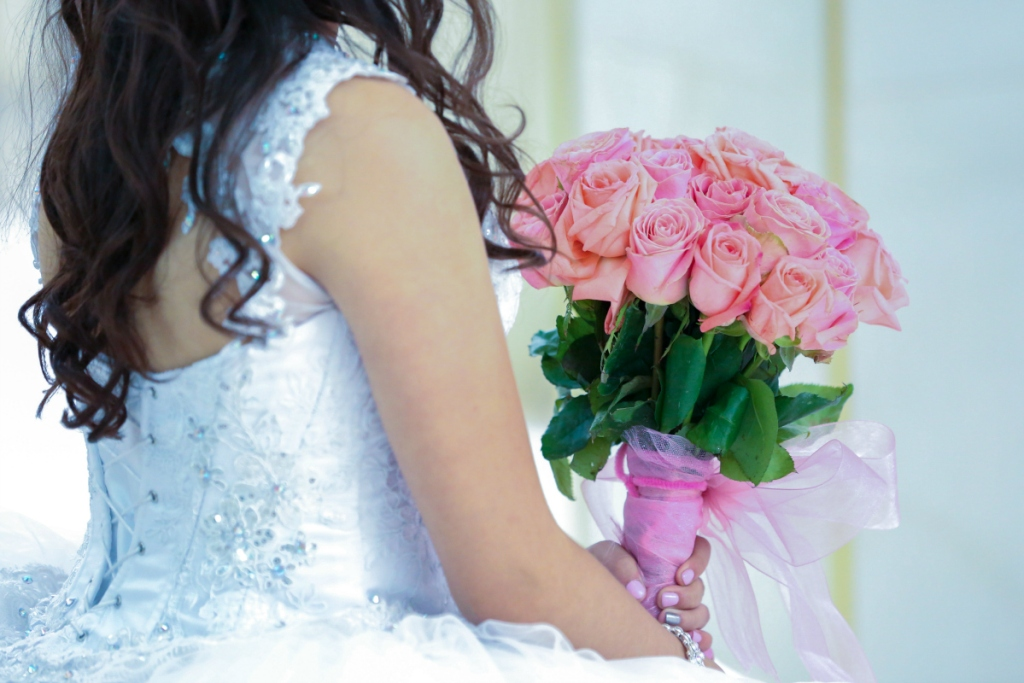 girl holding pink rose bouquet