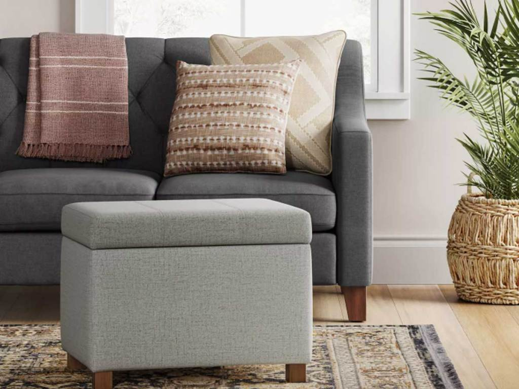 gray ottoman in front of a couch in a living room