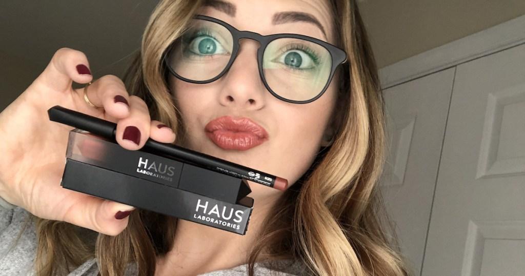 woman holding black haus laboratories makeup wearing glasses