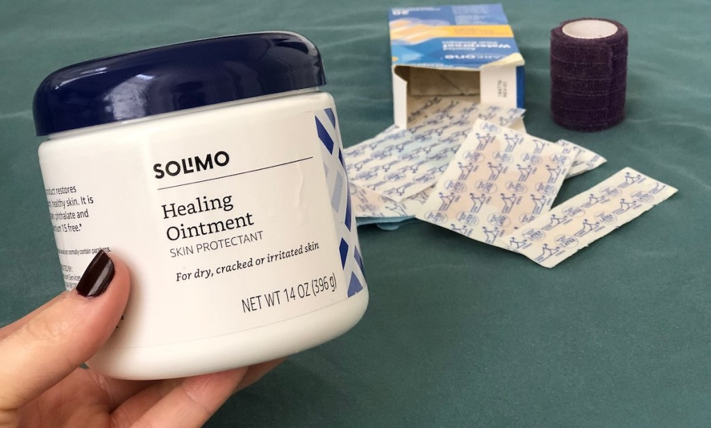 hand holding container of healing ointment with bandaids in background