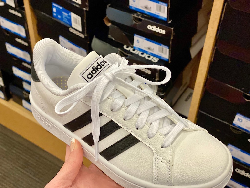 holding adidas white kids sneakers