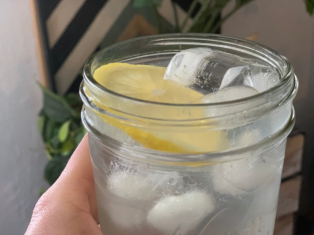 holding glass mason jar filled with water, ice, and lemon slice
