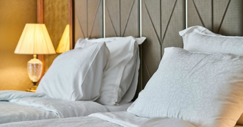 two beds with pillows and bedside lamp