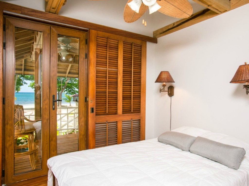 room with bed and doors to outside leading to beach
