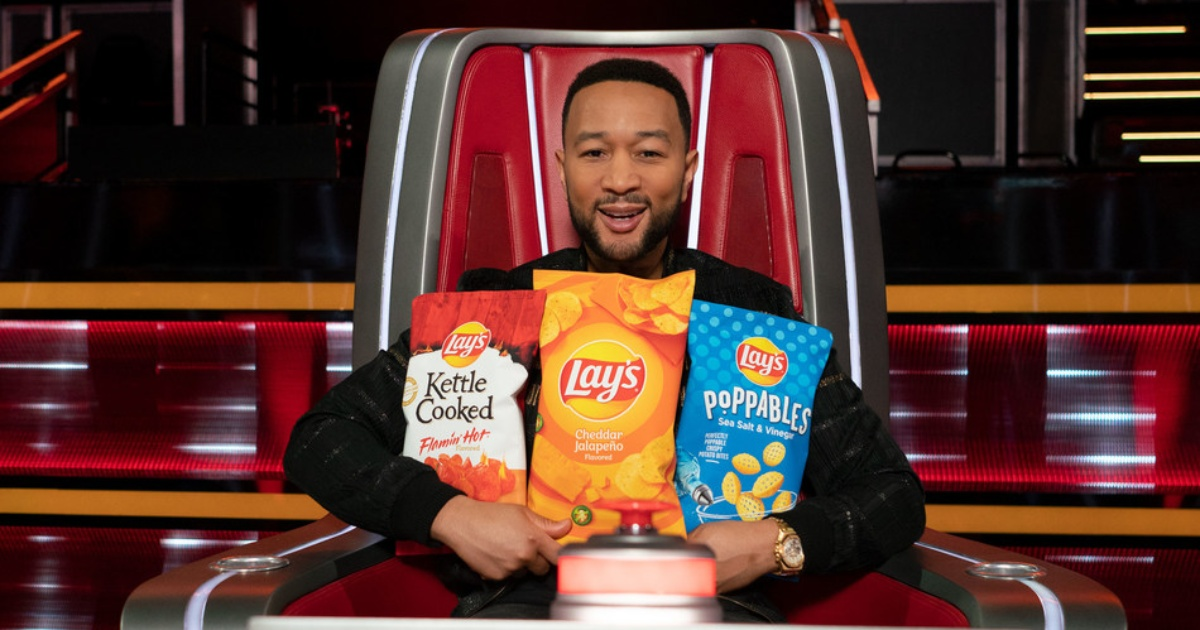 John Legend holding 3 bags of Lays potato chips
