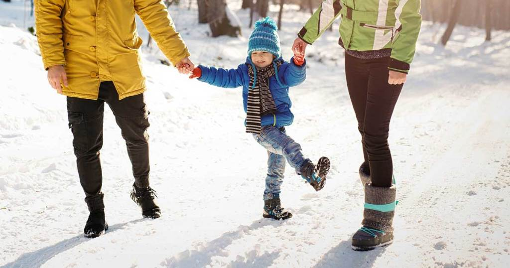 mom and dad walking with young child in the snow
