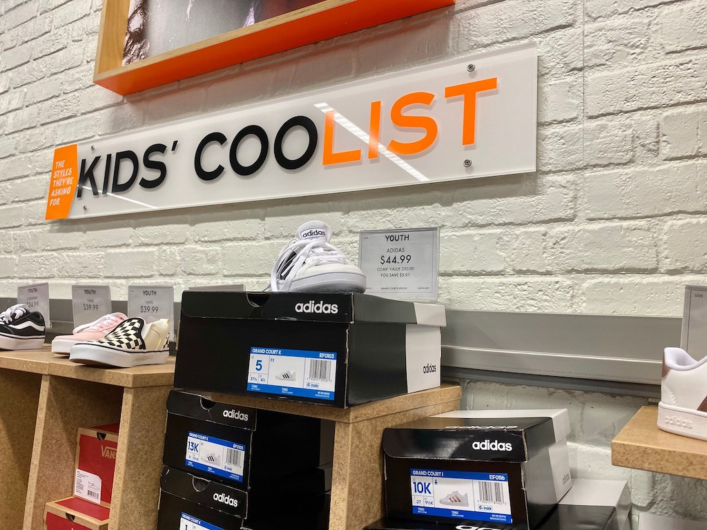 kids and youth shoe section at store with adidas and vans displayed