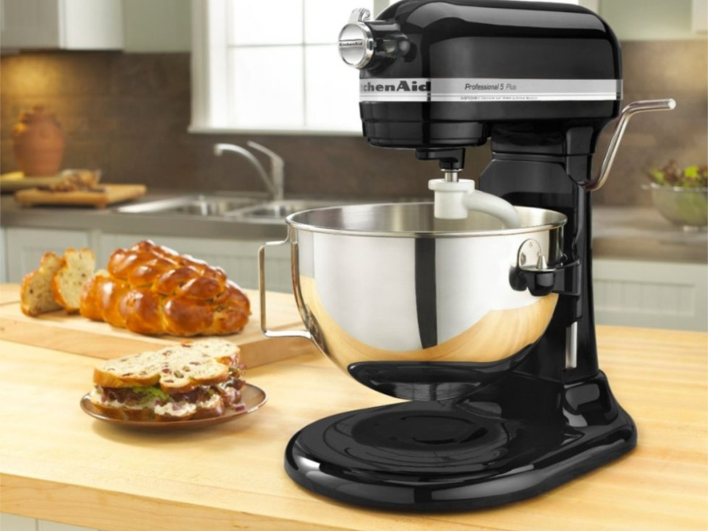 kitchenaid black stand mixer on counter in kitchen with food next to machine