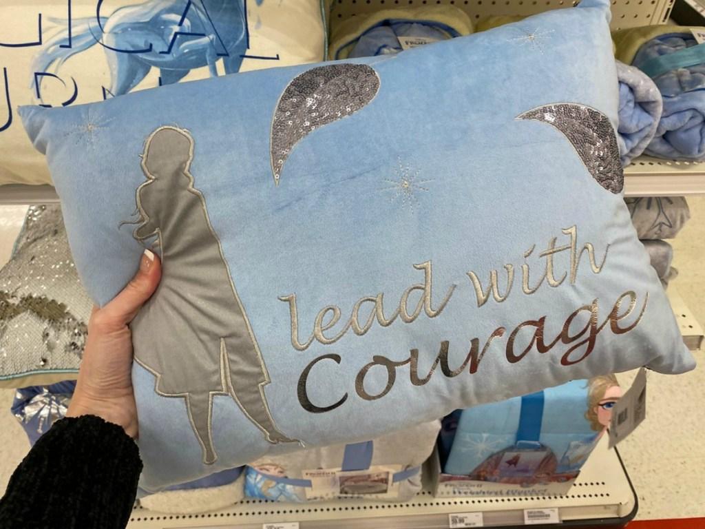 hand holding blue velvet pillow in store
