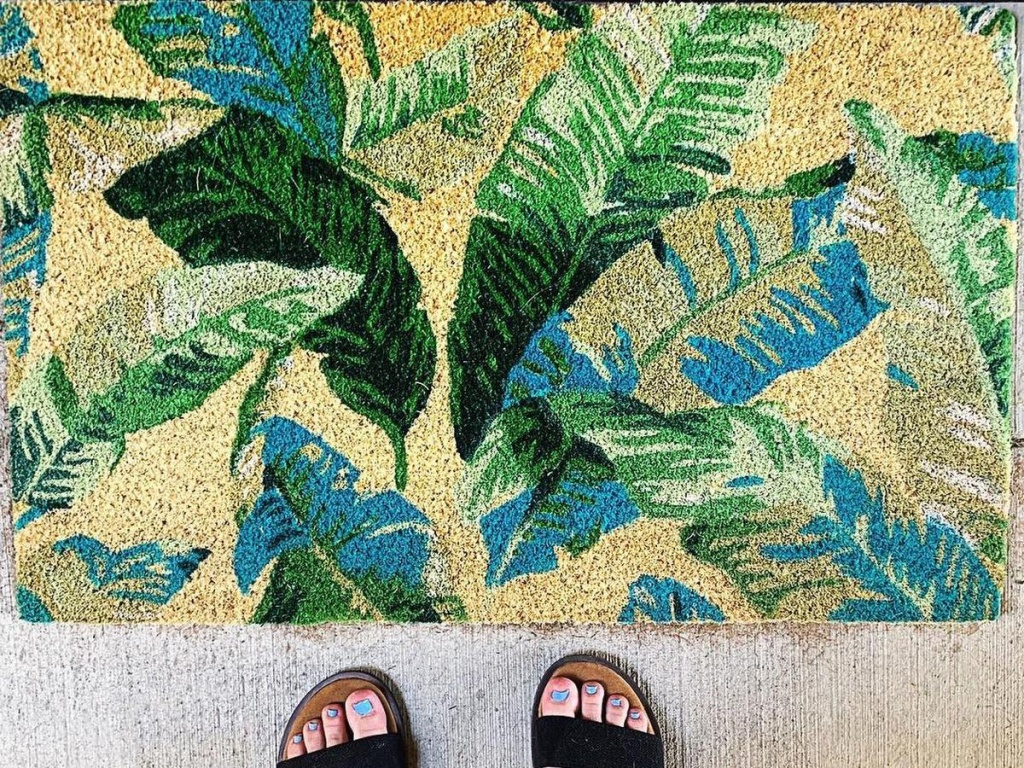 leafy rug with a woman's feet wearing black sandals by rug