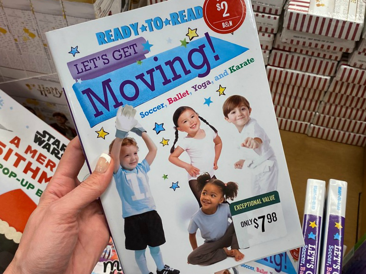 hand holding book showing little kids by store display