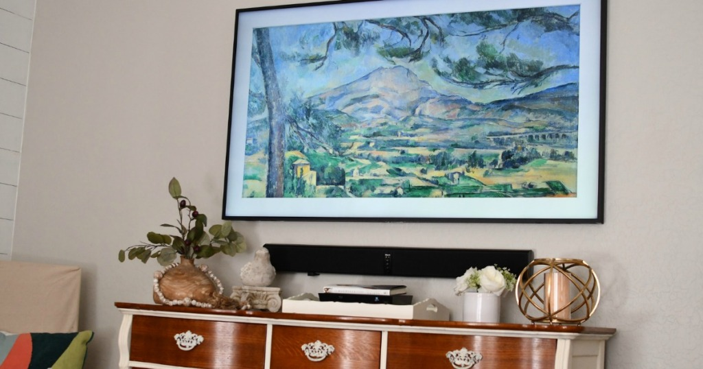 large TV that looks like art above furniture piece in living room