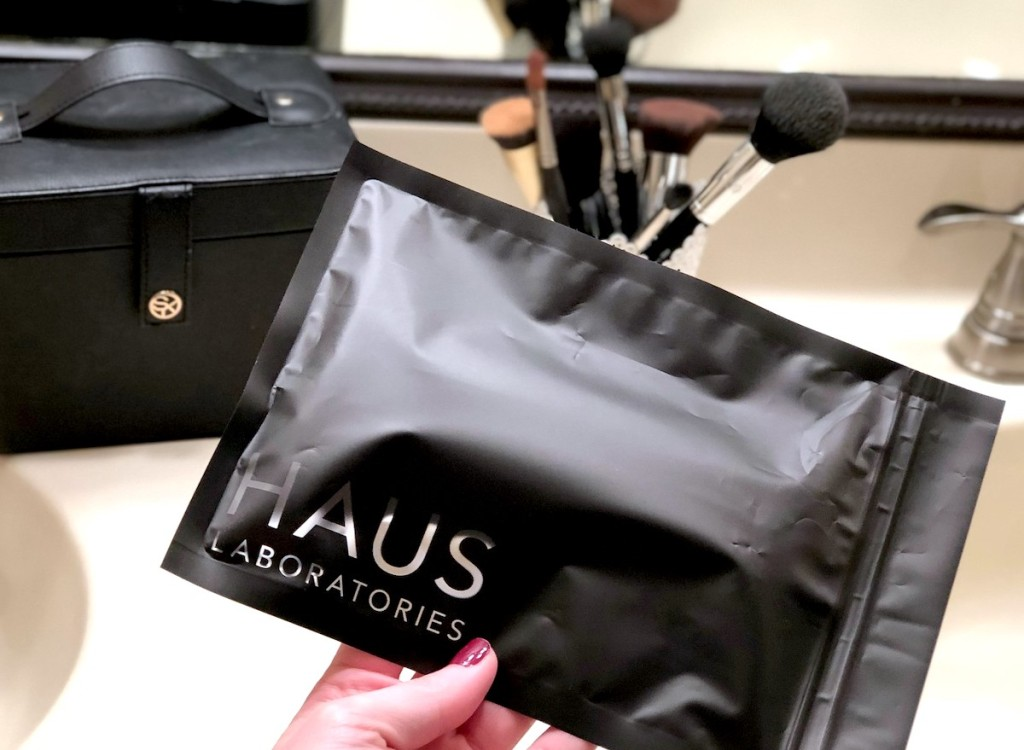 hand holding black haus laboratories bag with makeup brushes in background