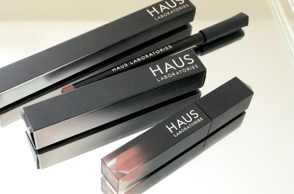 black makeup boxes with lip liner and lip gloss sitting on mirror