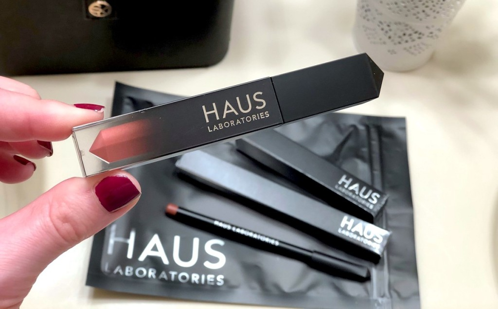 hand holding a haus laboratories lip gloss with makeup in background