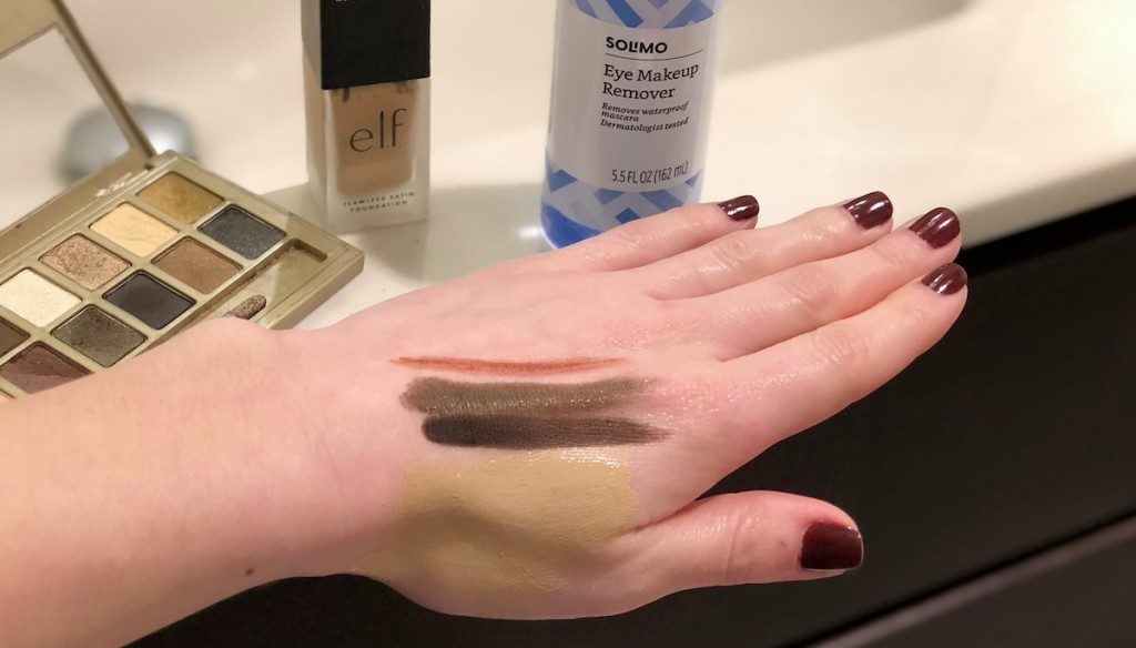 hand with various colors of makeup on it with cosmetics in the background