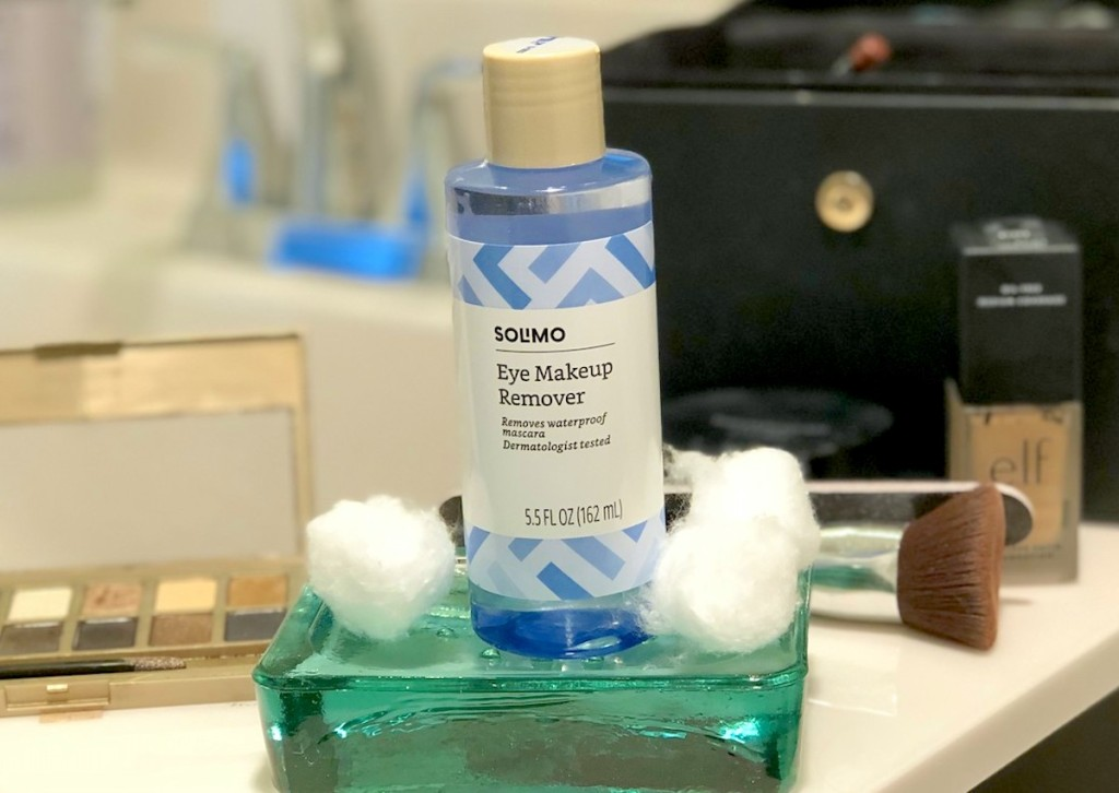 blue bottle of Solimo Amazon makeup remover sitting on bathroom counter with various types of cosmetics