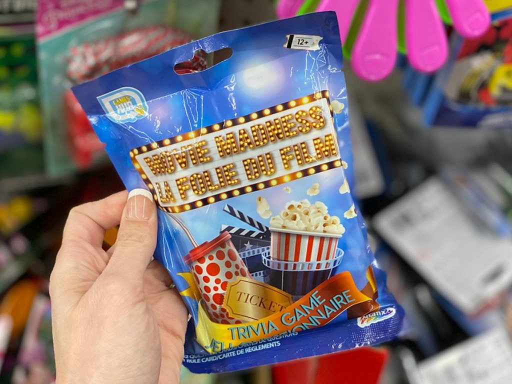 hand holding small package with movie trivia game inside