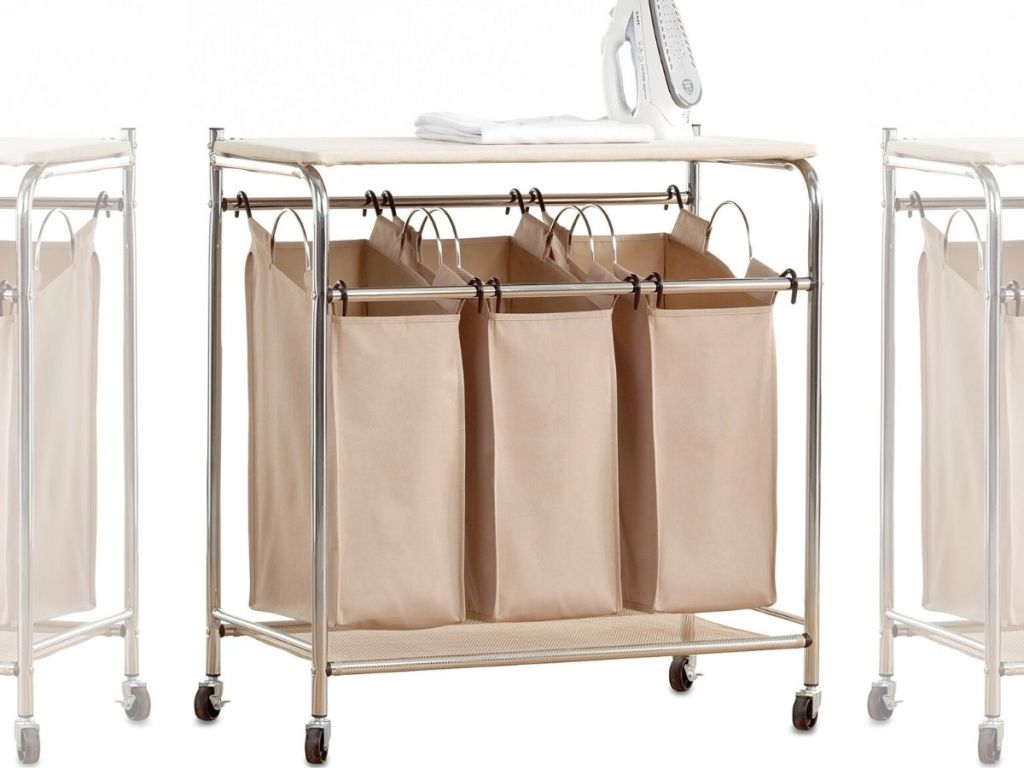 triple laundry sorter station with cloth hanging bags, metal frame and ironing board top with iron set on it