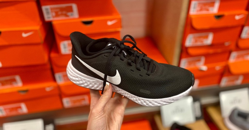 hand holding a black and white nike sneaker with orange nike boxes in the background