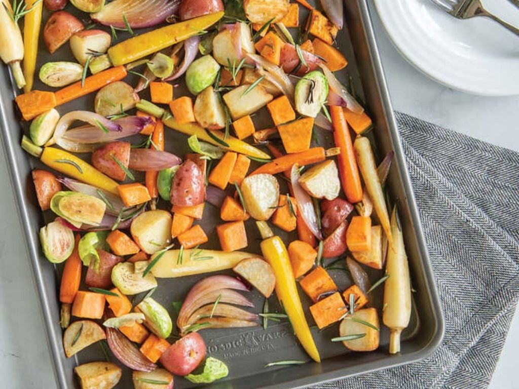 roasted vegetables on a baking sheet resting on a towel next to a plate with a fork