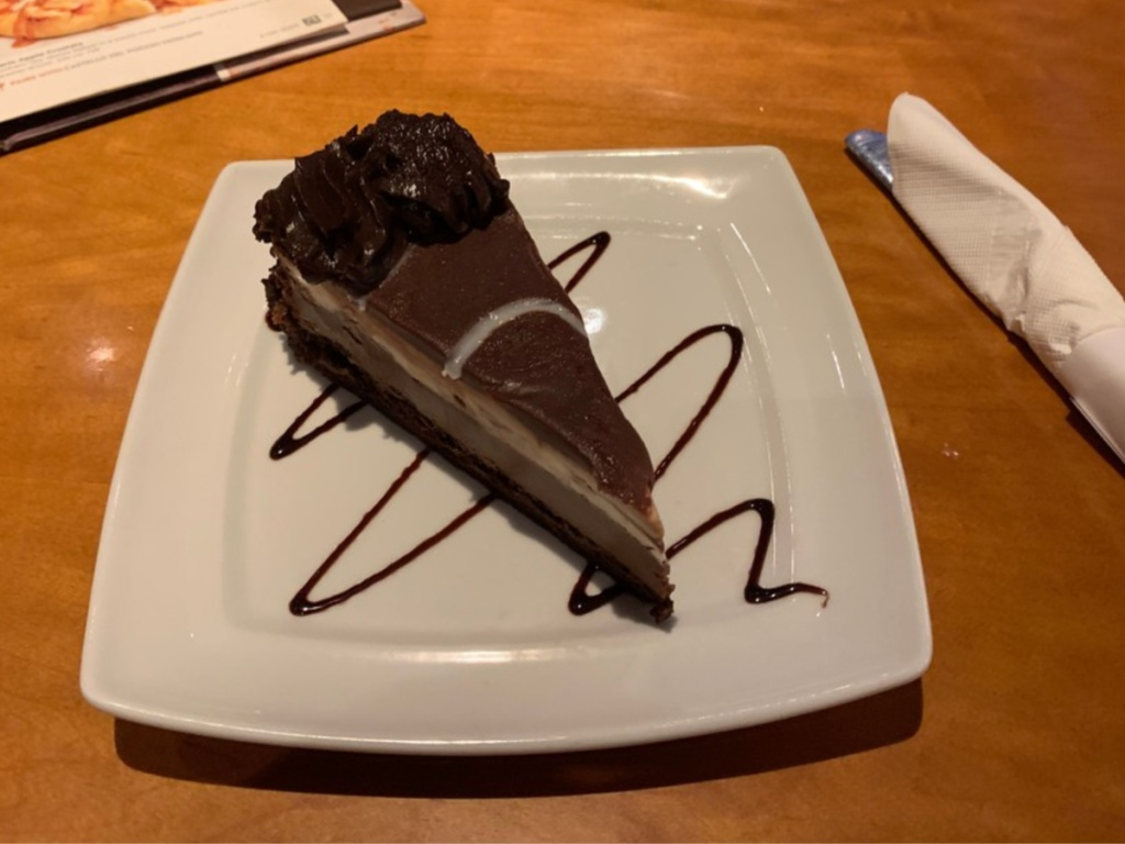 piece of chocolate cake/pie on white plate with chocolate swirl on plate