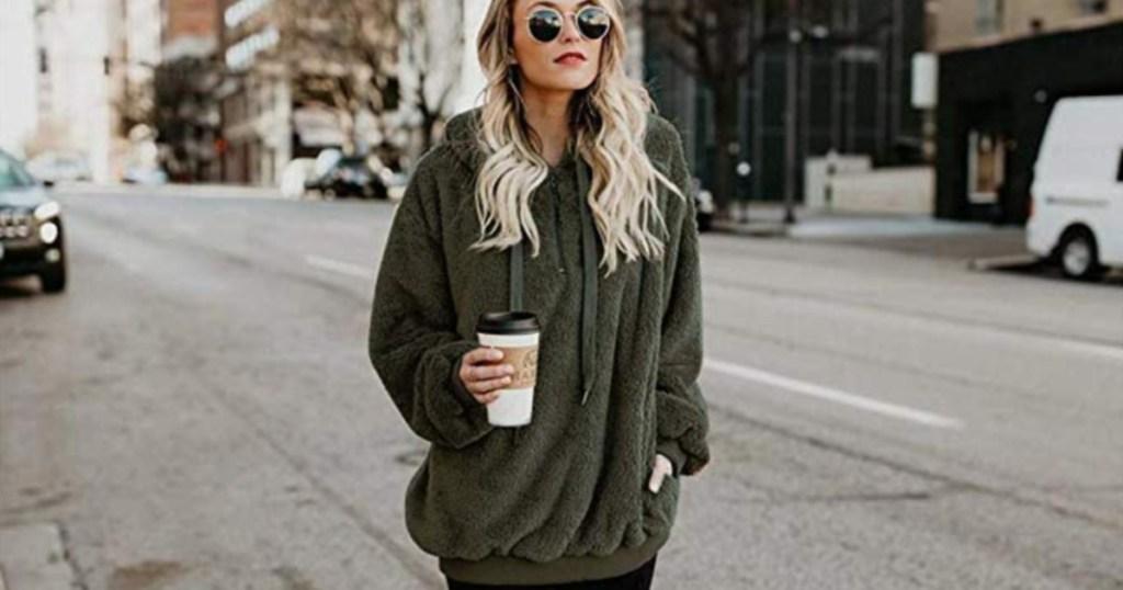 woman wearing a green sherpa sweater holding coffee