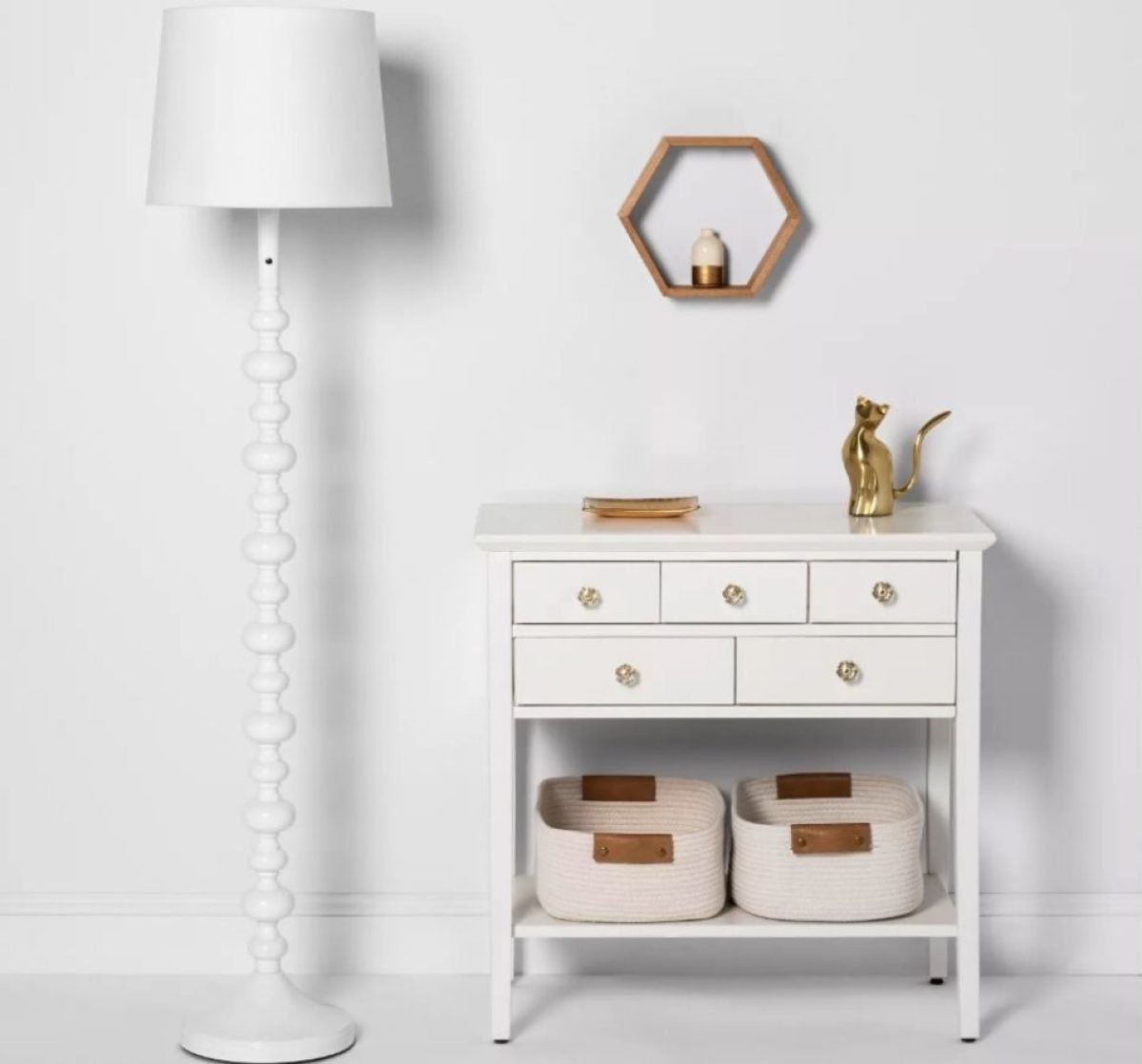 Floor lamp next to entry table with drawers, woven baskets on lower shelf, vase on top and mirror on wall above